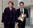 N-1165 In the given photo frame German Chancellor Angela Merkel along with the former French President Nicolas Sarkozy are probably going to meet the representatives of mass-media. Nicolas Sarkozy is carrying your photo. It is interesting why?